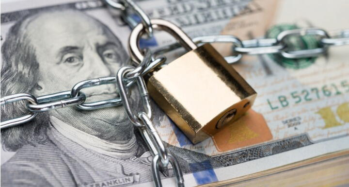 stack of money in chains with padlock