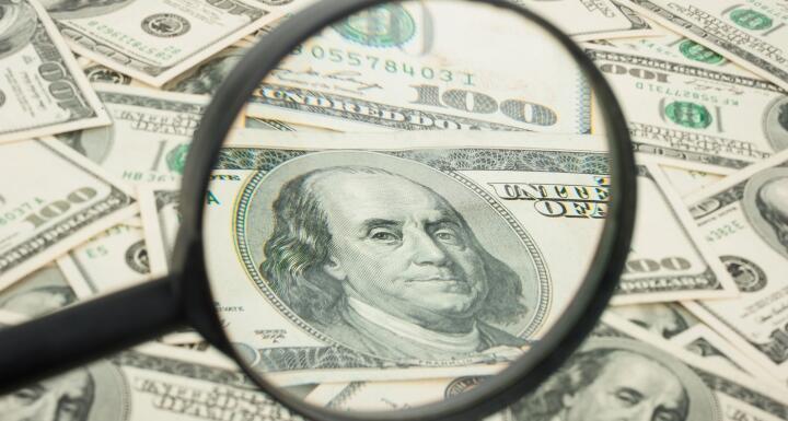 hundred dollar bill under magnifying glass