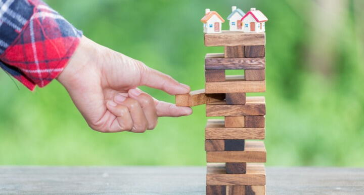 Toy houses on top of Jenga stack as hand pulls out a block