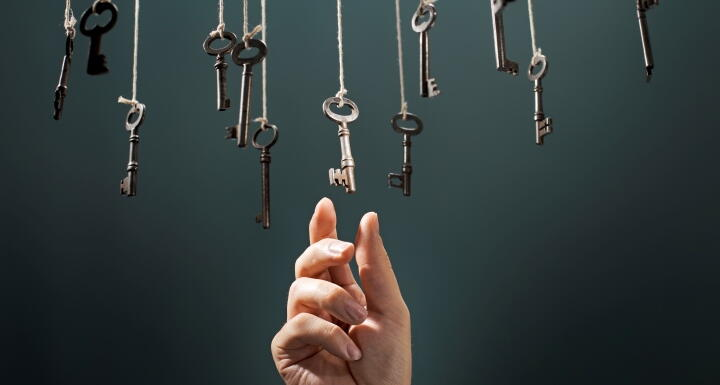 Keys hanging from ceiling as hand reaches up to grab one