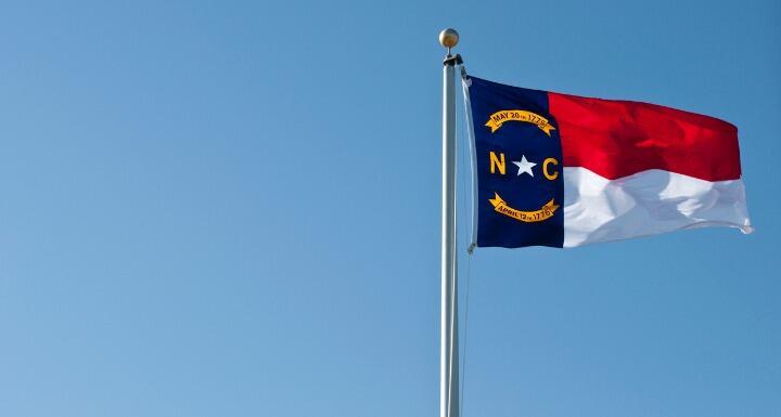 the North Carolina flag flying against a blue sky