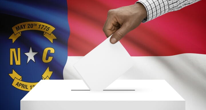 Person's hand dropping a white ballot into a white ballot box with the North Carolina State flag set as the back drop