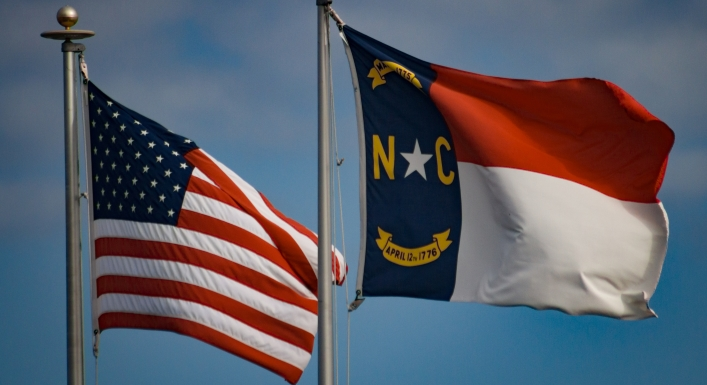 American and North Carolina flags waving in the wind