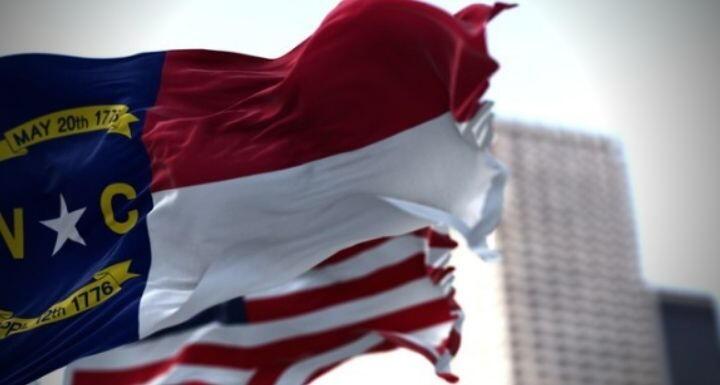 North Carolina state and American flag waving in the wind