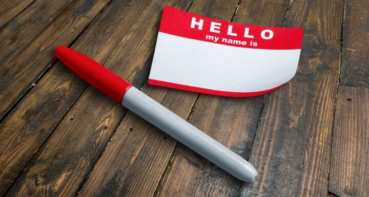 Red, blank name tag sticker beside a red pen