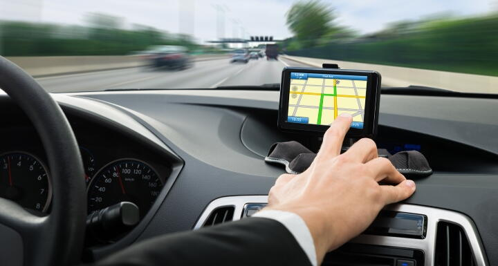 Man driving car while touching gps navigation screen