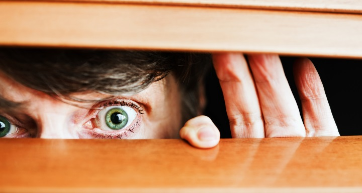A neighbor's eyes peeking through horizontal blinds