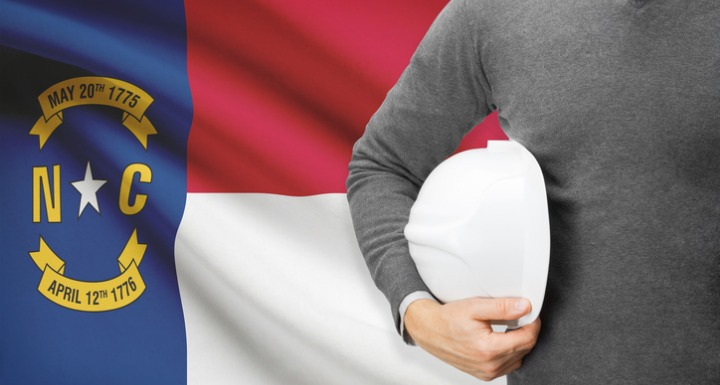 A man holding a white hard hat standing in front of the North Carolina state flag