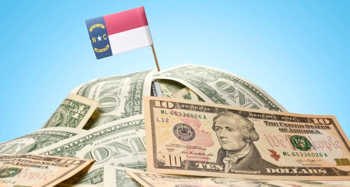 North Carolina Flag sticking in a pile of money