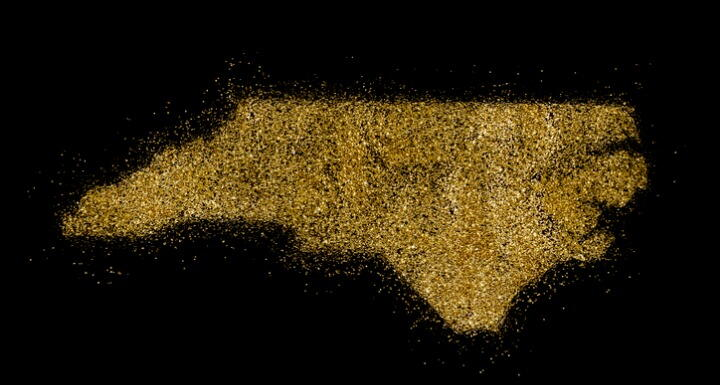 North Carolina shaped from gold glitter on a black background