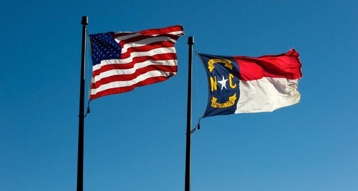 North Carolina and US flags against blue sky