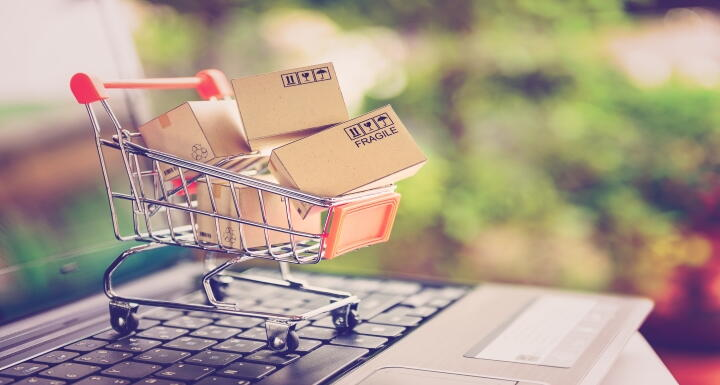 A small shopping cart full of tiny wrapped packages perched on top of a laptop's keyboard