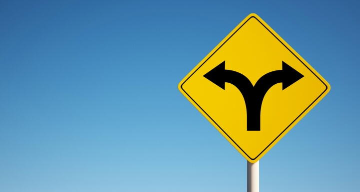 Road sign with arrows pointing in opposite directions