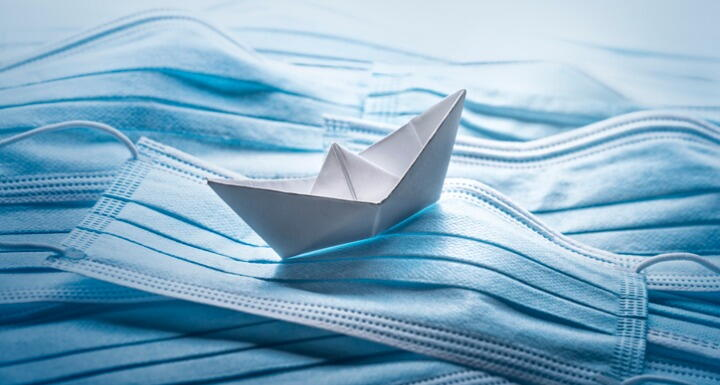 An origami ship that appears to float on a sea made of blue surgical masks