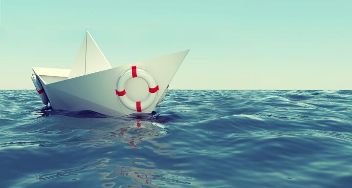A paper boat tossed on a blue sea
