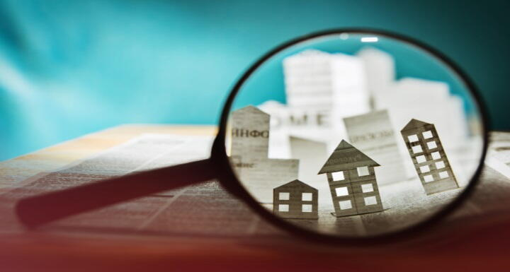 Magnifying glass focusing on houses cut out of paper