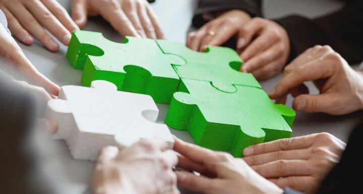 Business people assembling green and white puzzle