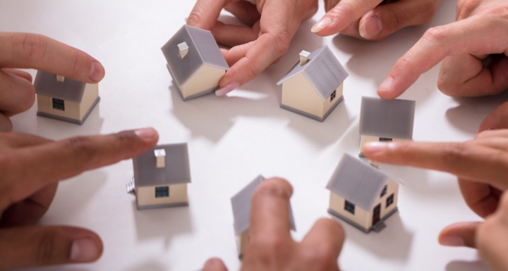 Hands moving mini homes around a white surface