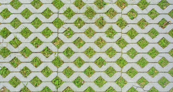 Permeable cement parking pavers with green grass growing in the holes