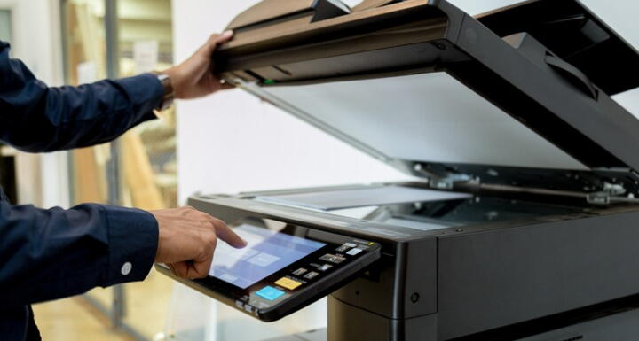 A person scanning documents on a large freestanding scanner-copier-printer machine