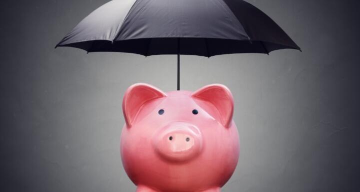 A pink ceramic piggy bank under a black umbrella signifying financial safety net