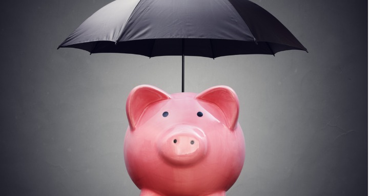 A pink ceramic piggy bank under a black umbrella signifying financial safety net