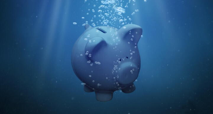 A piggy bank sinking under blue water