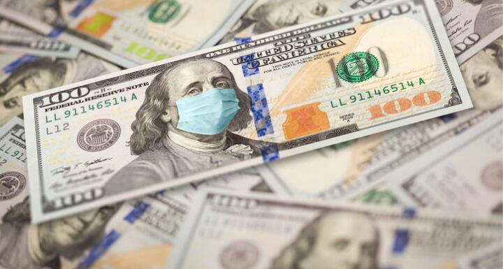 Pile of one hundred dollar bills with medical face mask on the Benjamin Franklin on the top bill