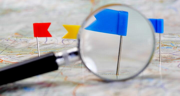Flag pins pushed into a map, with a magnifying glass highlighting a blue pin