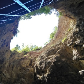 Cave or hole in the ground with sky in the background