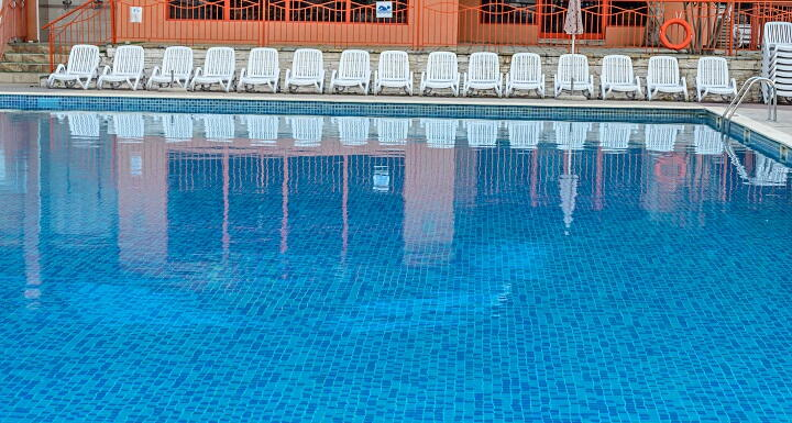 Inground pool with white chairs along surround deck