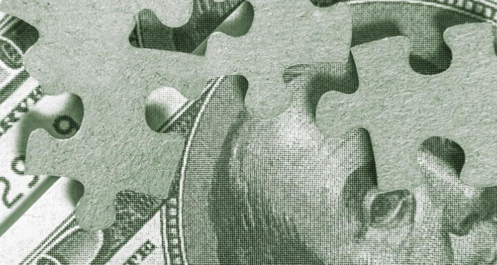 Puzzle pieces laying on top of a bill of money