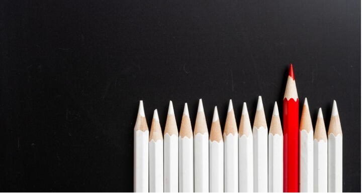 Line of white pencils all the same height with one red pencil in the middle and sticking up higher
