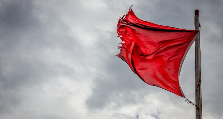 Red danger warning flag flying in high winds with storm clouds in the distance