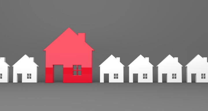 Red standout house in line with small white homes