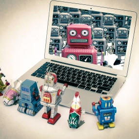 Robot toys surround a laptop with image of robot