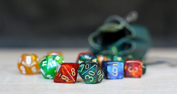 Colorful dice from various games spilled onto a table top