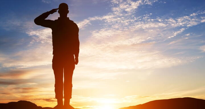 silhouette of a soldier standing and saluting with a sunset in the background