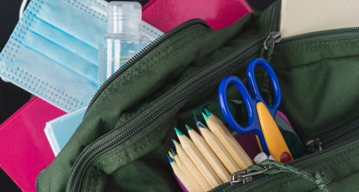 A student's backpack with pencils, scissors, hand sanitizer, and a medical mask