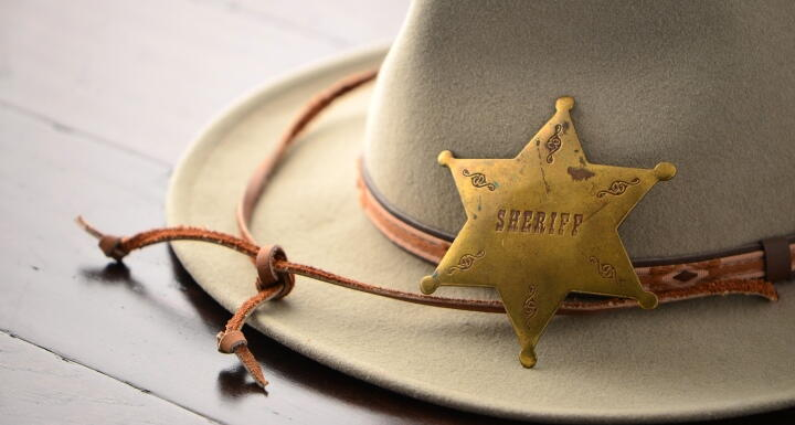 Brown sheriff hat with a badge laying on top