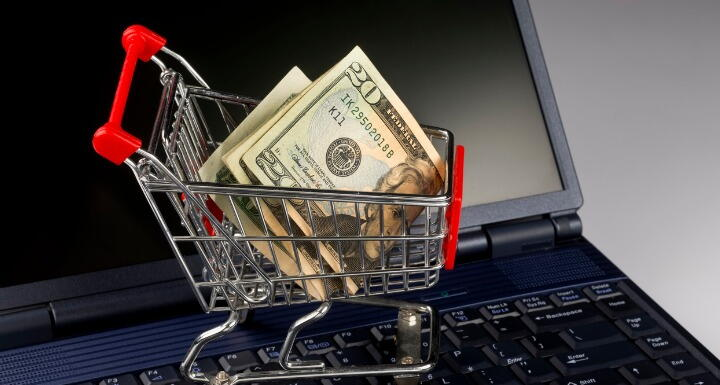 Tiny metal shopping cart sitting on the keyboard of a laptop with folded twenty dollars in it