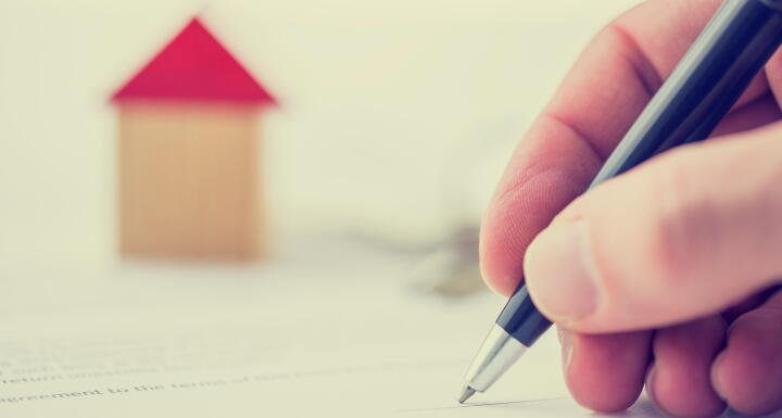 Hand signing the deed to a house with a house in the background