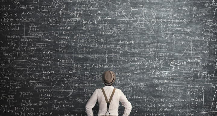 Man facing large chalkboard covered in math equations