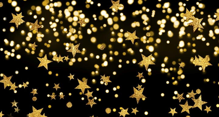 Dozens of sparkling gold stars falling in front of a black back ground