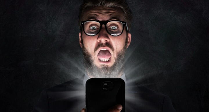 A Surprised man looking a phone