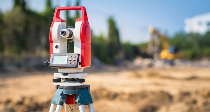 A red surveyors tripod set up on a large construction site