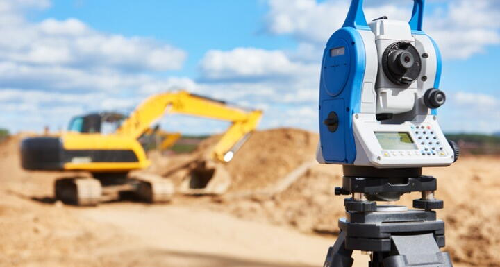 Surveyor equipment in the foreground with a yellow construction truck in the background
