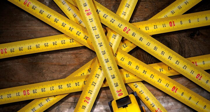 Several measuring tapes arranged in a starburst pattern on a wooden floor