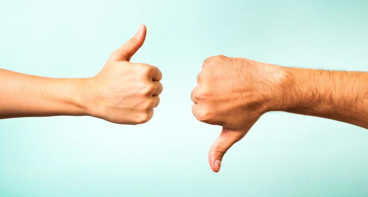 Two hands with one showing thumbs up and one showing thumbs down