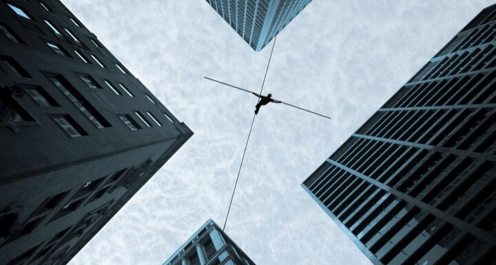 Bottom up view of a person on tightrope walking between buildings